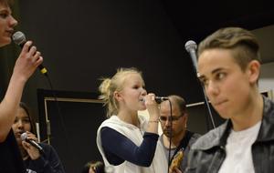Rebecca Frisk i kören sjunger tillsammans med Oliver Lindberg och Emma Karlsson. I förgrunden syns skådespelaren Love Ekberg.
