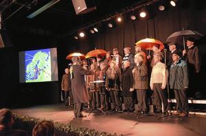 Strilande jul. En nyskriven sångtext                            beskrev väderleken som den ofta brukar vara på julafton. Vinterklädda körsångare illustrerade                                 med paraplyer.