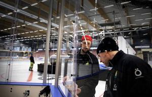 Markus Åkerblom och materialaren Daniel Andersson sätter på reklam på sargen.