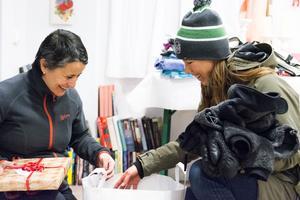 Carla Dahlberg och Helena Stenport packar upp kläder och julklappar som Helena har lämnat.