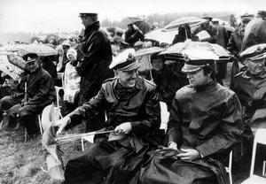 1979. Kungen i blåsväder. Det blåser och regnar rejält under flygdagen då F1 firar 50-årsjubileum. Högtidsklädseln består av regnställ, stövlar och paraplyer. Flygvapenchefen Dick Stenberg ser glad ut ändå.