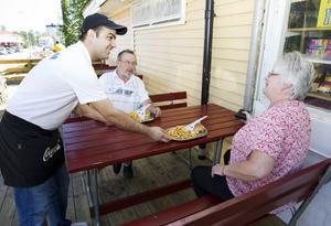 Diyar Ghaderi serverar hamburgare med pommes till Torbjörn Bergström och May Palm.