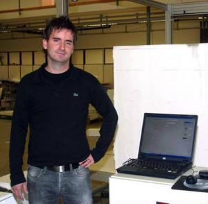 Lars Edfeldt, vd för Flooré i Ånge med den nya maskinen som skär till den storlek av golvvärmeplattor som kunden vill ha.
