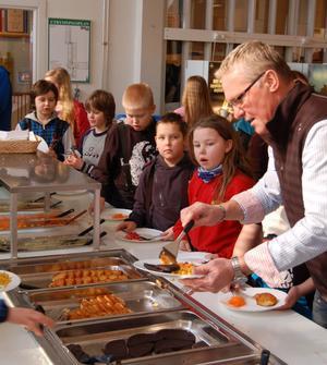 Nu äter kommunalrådet tillsammans med skolbarnen i Älvdalsskolan. Här står han i kön till blodpudding och potatisbullar, som serverades på torsdagen.
