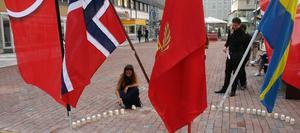 Vanja Ahlén, ombudsman för Socialdemokraterna i Västerås, tänder ljus för att hedra de avlidna. Till höger står Martin Andersson, distriktsordförande SSU i Västmanland.