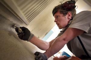 Golvläggaren Markus Persson stryker ut golvet som består av flytande akrylplast blandad med färgad kvartssand.