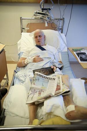 Från sjuksängen håller Åke sig uppdaterad med surfplatta, mobiltelefon och kvällstidning.