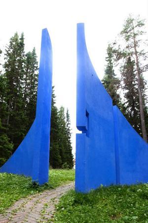 Mellan tallarna och granarna skymtar Blå Porten, som inleder konststigen som slingrar fram genom Torvallas skog.