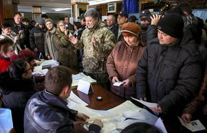 President Porosjenko (uniform) besöker en vallokal i östra Ukraina.