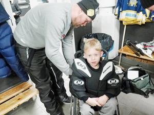 Pappa Fredrik hjälper Mille att få på sig alla målvaktsskydd inför matchen.