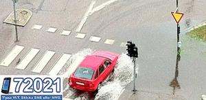 Blött en dag. En bil forcerar en vattensamling vid Emausgatan.