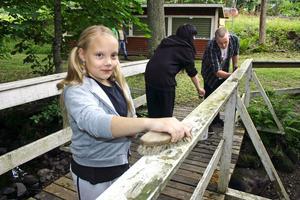 Melinda Berger tvättar träräcket runt festplatsen i Gropen.