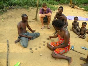 EN familj från Ghana spelar ett spel i sanden.