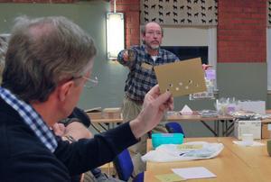 Auktionen kan börja. Tomas Rydin höjer klubban och hugade frimärksspekulanter höjer auktionskorten.