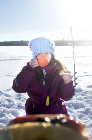 Här sitter en nöjd storfiskare. I stället för abborre på grillen blir det korv med bröd och en kopp varm choklad.