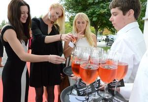 Servering. Studenterna Linda Hammargren, Emelie Persson och Denise Olsson Galli serveras av gymnasieeleven Andreas Norling.