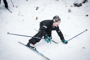 Edwin Bergström öser på i den lilla nedförsbacken på skidspåret och gör en vurpa medan han skrattar.