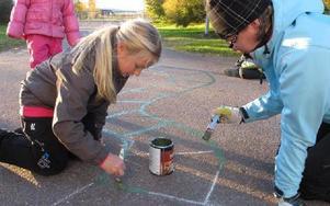 En bokstavsorm tar form. Alva Lundin och Carina Åkerström målar.Foto: KARIN SUNDIN