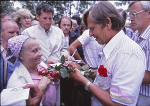 En kvinna får en autograf efter talet i Badhusparken.