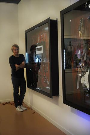 – Tanken med utställningen är att visa upp det jag håller på med. Det finns mycket inom konsten jag vill göra. Samtidigt vill jag bli klar med min bok, säger Erik Olof Wiklund här vid sina två objekt med bland annat en deformerad elgitarr.