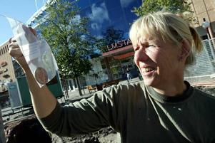 Arkeologen Ylva Roslund-Fornelius visar upp ett mynt från tiden kring 1640, som hittades under stenbeläggningen på Stortorget.