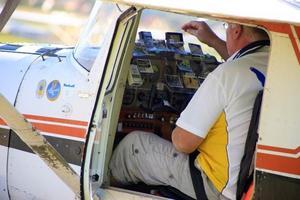 Lars-Inge Karlsson, Gävlebygdens Flygklubb, förbereder sig inför tävling genom att sätta upp foton på observationspunkterpå instrumentpanelen i planet.