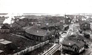Så här såg det ut på Alderholmen för ungefär 110-120 år sedan. Och de här byggnaderna har vi identifierat med hjälp av Robert Herpai på Sveriges Järnvägsmuseum:1. Gävle-Dala Järnvägs lokstallar. Det är inte de som i dag utgör en del av järnvägsmuseet vid Sörby Urfjäll. Den här byggnaden revs förmodligen på 1950-talet.2. Godsvagnsverkstaden. Flyttades till Nynäs omkring 1905.3. Förrådsbyggnad som på sin tid var en aning märkt av stadsbranden 1869.4. Gamla verkstaden.5. Hotell Fenix.6. Godsmagasinet. Skymmer det mesta av Fenix.7. Vagnverkstaden. Flyttades till verkstaden på Nynäs när den blev klar runt 1905.8. Toalettbyggnader som numera finns i Boulognerskogen.