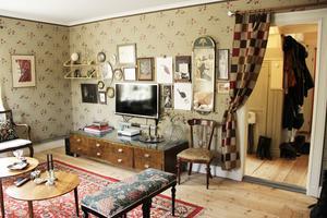Salen eller vardagsrummet har en mullvadsgrå tapet med svarta detaljer och röda blommor. Den heter Katarina och är en nytillverkning av en tapet från 1920-talet.