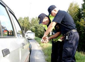 Trafikpolis Lennart Norlander och bilinspektör Torbjörn Wahlqvist diskuterar däckens mönsterdjup på en av de stoppade bilarna.