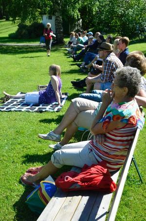Blandade åldrar på publiken på bänkar och i gröngräset.