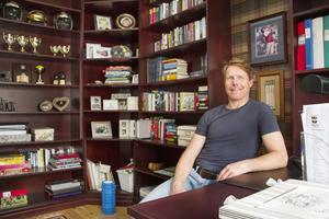 Andreas i biblioteket med böcker och hockeytroféer.