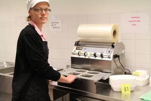 Maria Johansson visar hur det ser ut i packrummet. Arbetsbänken är höj- och sänkbar och här svetsar man plast på matlådorna, som ska ut. Tre personer jobbar varje dag med att packa matlådorna och få ut dem i tid.