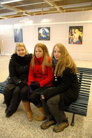 Emelie Levin, Lova Viktorsson och Kata Säfve är tre av de bildelever som ställer ut sina konstverk hos konsklubben Blå soffan under januari. Här sitter de på just den blå soffan.