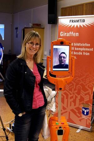 Marika Olofsson, enhetschef inom LSS, står tillsammans med roboten Giraffen. Roboten styrs av Kjell Thuné, som syns på bild på robotansiktet. Roboten kan röra sig runt i lägenheten och är tänkt att kunna underlätta kontakt med äldre, både från anhörigas och hemtjänstpersonals sida.