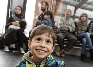 Lille Ayham är glad över att vara i Sverige. I bakgrunden syns familjen. De kommer alla från Syrien.