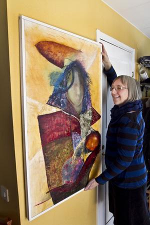 Margareta rättar till en av sina målningar.