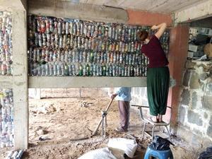 Petflaskor fyllda med skräp fyller väggarna i skolbygget. Det tar femtio minuter att fylla en petflaska.