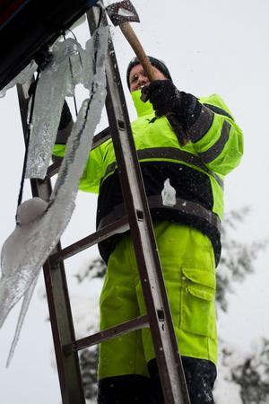 Tony Larsson använder baksidan av en yxa för att hacka is utanför badhusets handikappentré.