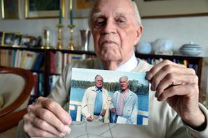Alf Cederlind visar upp en bild på sig själv och tvillingbrodern Erik. I dag fyller de 90 år.BILD: BJÖRN PALMQVIST