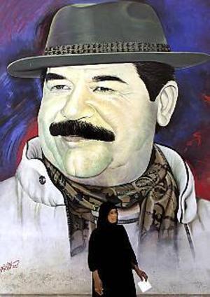 Foto: SCANPIX Personkult. En irakisk kvinna framför en av många jättelika målningar av Saddam Hussein. Personkulten påminner inte så lite om de som omgärdat tidigare diktatorer.