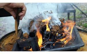 Myrmalmen rostas över öppen eld. -- Det måste vara 700 grader varmt för att få en kemisk reaktion så myrmalmen blir magnetisk och järnpulver bildas. FOTO: ANGELICA LINDVALL