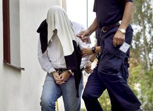 Den åtalade 45-åringen poliseskorteras in till Hudiksvalls tingsrätt, den första rättegångsdagen.