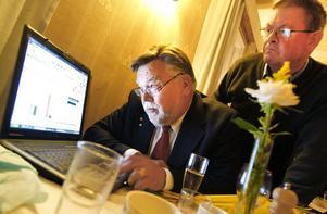 Håkan Rönström (M) håller koll på den preliminära mandatfördelningen. Enligt den tycks inte Moderaterna få fler mandat i kommunfullmäktige, trots att rösterna ökat med 1,8 procentenheter. På bild även Anders Bengtsson.