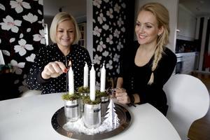 Snart kan Tina Persson och Jessica Engström tända första adventsljuset.   Adventsljus i kattmatsburkar: Ta bort etiketterna från fyra burkar och fyll dem med sand. Högst upp läggs lite vanlig mossa. Dekorera med kottar som är sprayade med konstnö. Märk varje burk med dymotext.