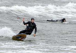 Vågsurfare och kitesurfare samsas i vattnet. Urban Lind i dagens första åk.