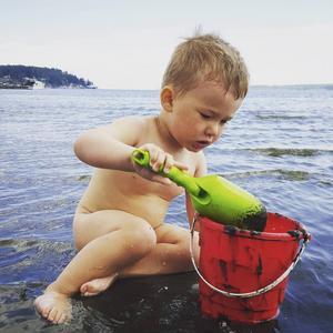 En nakenfis som leker på badstranden i Bergafjärden.