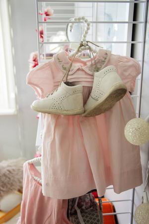 En urvuxen babyklänning och ett par av Sigrids första skor hänger framme som dekoration.