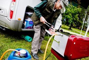 Rudolf Weisskopf från Basel i Schweiz var ensam grillare på Östersunds camping under den kyliga gårdagskvällen. I dag lär desto fler ställa sig framför grillen. – Ha en hink vatten i beredskap och vänta med drickandet till efter grillningen, tipsar Anders Elnerud. Foto: Lars-Eje Lyrefelt