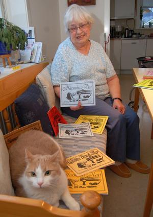 Rut Puck Olsson fick på tisdagen ett fint pris för sina böcker om Mumunes Masse, här med sin egen Masse och några av 45 varianter av hennes böcker på olika dialekter i kökssoffan i Älvdalen.