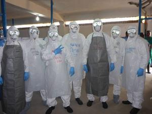 Sjuksköterskan Leif Isaksson (trea från höger i grått förkläde) och kollegor från Kuba iförda skyddsdräkter. Redan efter 15 minuter är de så svettiga att skyddsglasögonen immar igen.
